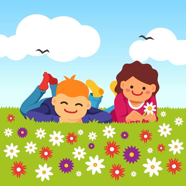 Enfants heureux posés sur l'herbe de prairie Vecteur gratuit