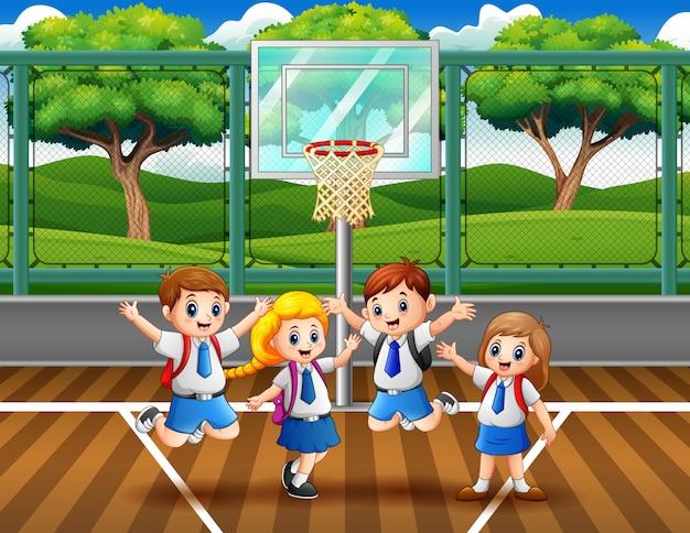 Enfants heureux en uniforme à sauter sur le terrain de basket Vecteur Premium