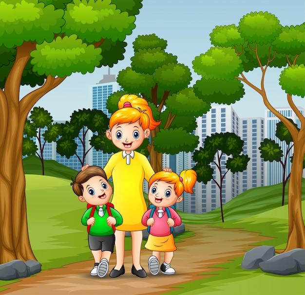 Des enfants heureux vont à l'école avec maman Vecteur Premium