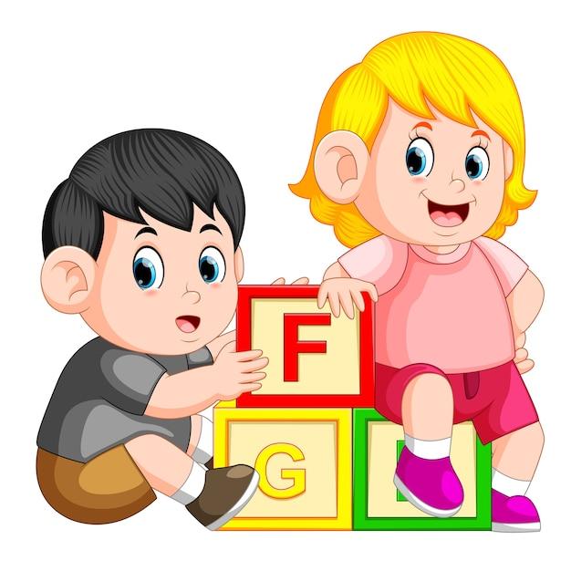 Enfants jouant avec bloc alphabet Vecteur Premium