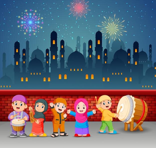 Les enfants plaquent les outils de musique dans la nuit du ramadan Vecteur Premium