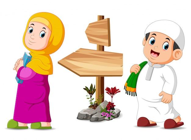 Les enfants posent près du poteau en bois Vecteur Premium