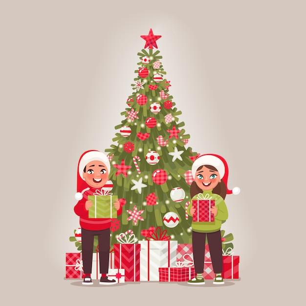Enfants Et Sapin De Noël Décoré. Un Garçon Et Une Fille Tiennent Des Cadeaux. Joyeux Noel Et Bonne Année Vecteur Premium