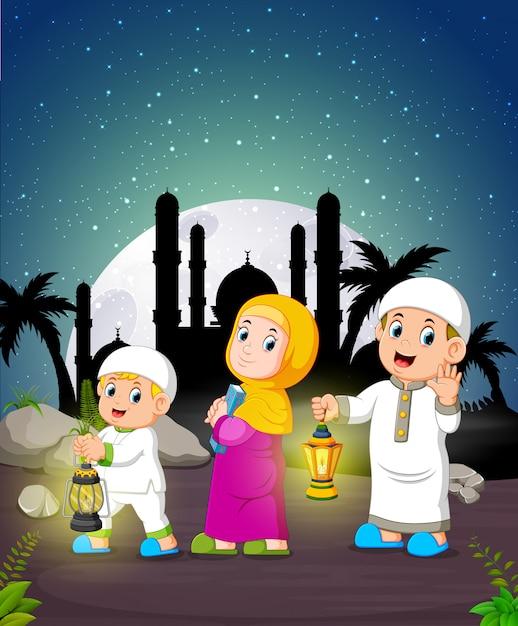Les enfants tiennent la lanterne du ramadan au clair de lune Vecteur Premium