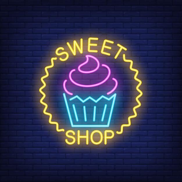 Enseigne au néon magasin de bonbons. cupcake savoureux dans le cercle de la vague. nuit lumineuse Vecteur gratuit