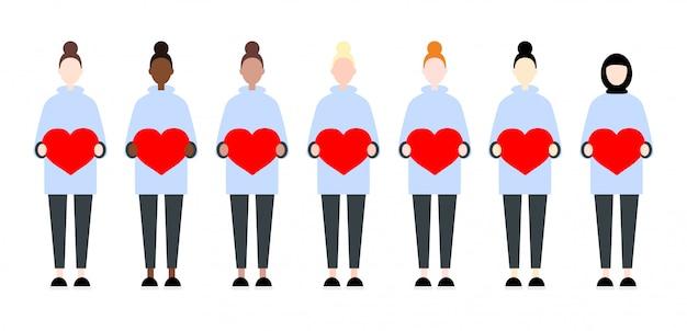 Ensemble de femmes de vecteur de race diverses tenant des coeurs. saint valentin style plat mignon et simple Vecteur Premium
