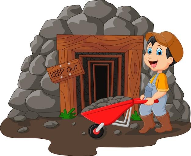 Entrée de la mine de dessin animé avec un mineur en possession d'une pelle Vecteur Premium