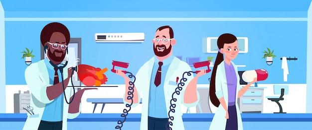 Équipe de médecins détenant des équipements pour la réanimation cardiaque Vecteur Premium