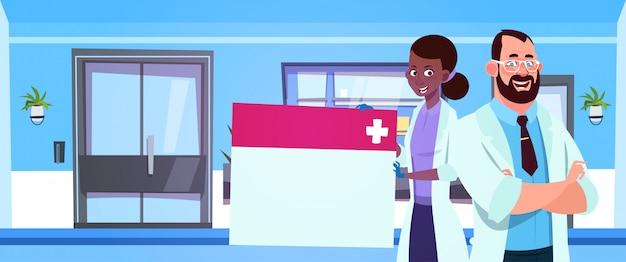 Équipe de médecins tenant un tableau vide Vecteur Premium