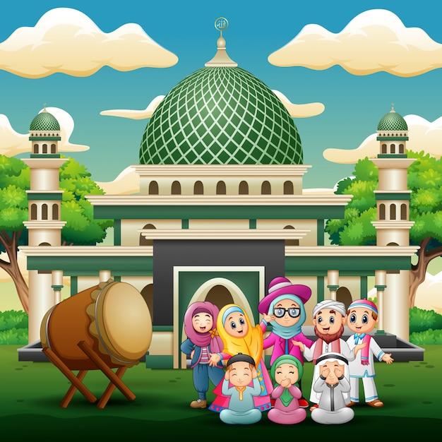Famille heureuse fête pour l'aïd moubarak devant la mosquée Vecteur Premium