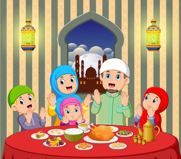 Une famille heureuse prie avant de manger dans sa maison avec une vue magnifique depuis la fenêtre Vecteur Premium