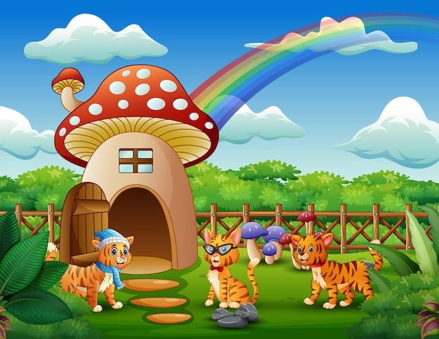 Fantaisie maison de champignon avec trois chats Vecteur Premium