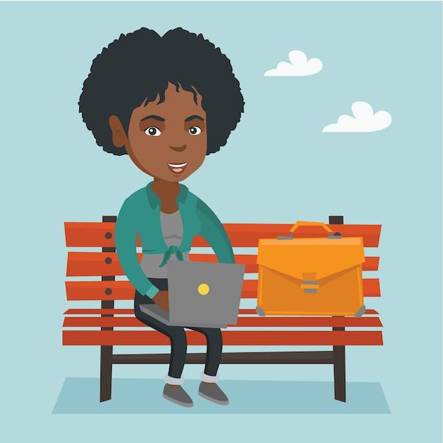 Femme d'affaires africaine travaillant sur un ordinateur portable en plein air. Vecteur Premium