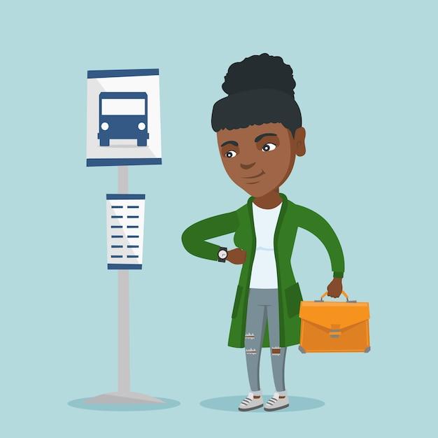Femme africaine attendant un bus à l'arrêt de bus. Vecteur Premium