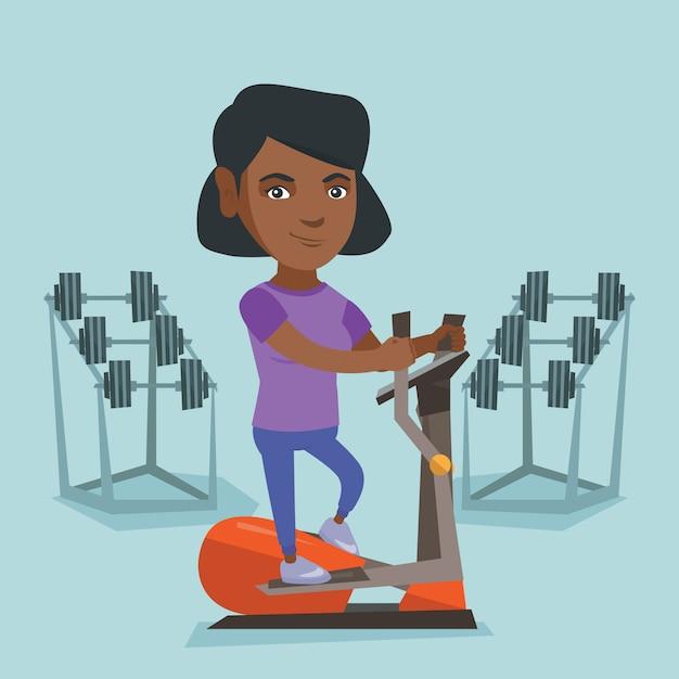 Femme africaine exerçant sur vélo elliptique. Vecteur Premium