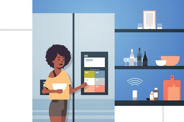 Femme Afro-américaine, Toucher, écran Réfrigérateur, à, Haut-parleur Intelligent, Reconnaissance Vocale Vecteur Premium