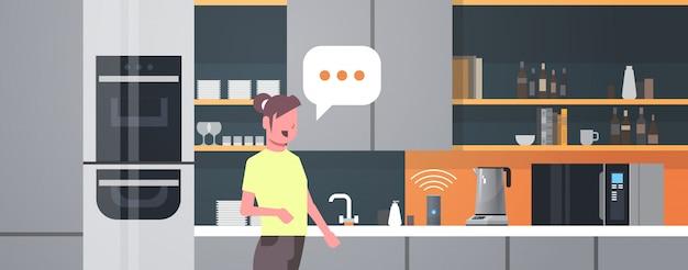 Femme Au Foyer à L'aide De Haut-parleur Intelligent Reconnaissance Vocale Activé Assistants Numériques Automatisé Commande Rapport Concept Cuisine Moderne Intérieur Plat Horizontal Portrait Vecteur Premium