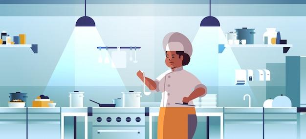 Femme Chef Professionnel Cuisiner Préparer Et Déguster Des Plats Femme Afro-américaine En Uniforme Près Du Poêle Cuisson Concept Alimentaire Restaurant Moderne Cuisine Intérieur Plat Portrait Horizontal Vecteur Premium