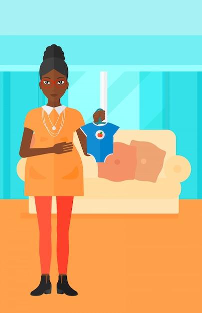 Femme enceinte avec des vêtements pour bébé. Vecteur Premium
