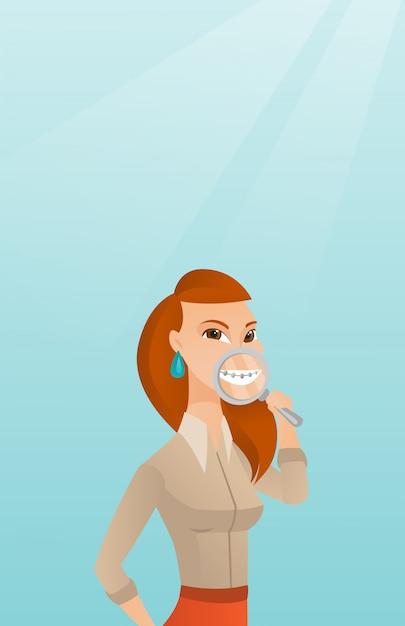 Femme examinant ses dents avec une loupe. Vecteur Premium
