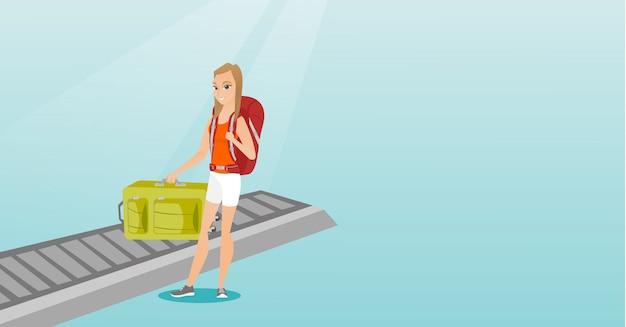 Femme ramassant la valise du tapis roulant. Vecteur Premium