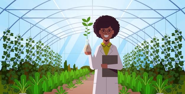 Femme Scientifique Examinant Un échantillon De Plante Dans Un Tube à Essai à L'intérieur De La Serre En Verre Moderne Vecteur Premium