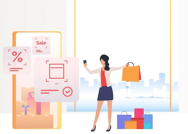 Femme tenant un sac et des achats sur smartphone en ligne Vecteur gratuit