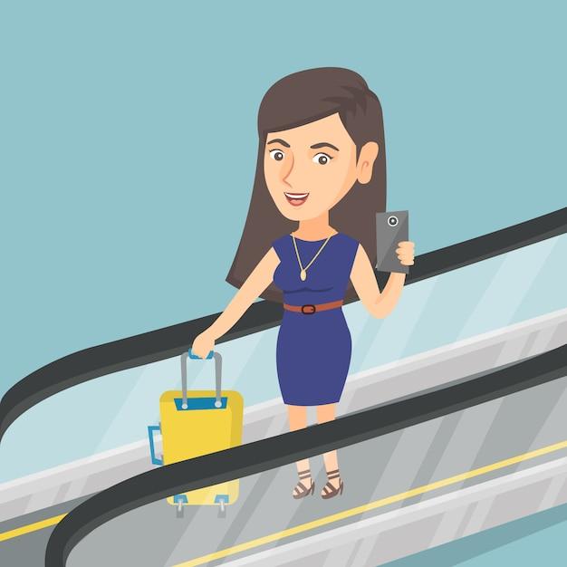 Femme, utilisation, smartphone, escalator, aéroport Vecteur Premium