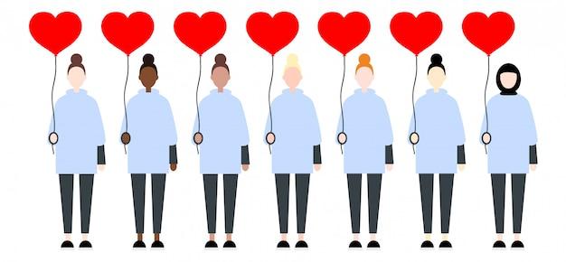 Femmes dans des vêtements décontractés, tenant des coeurs de ballon rouge Vecteur Premium
