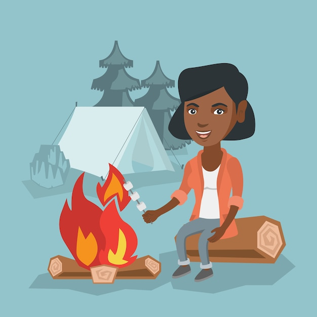 Fille africaine rôtir la guimauve sur le feu de camp. Vecteur Premium