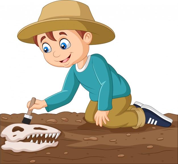 Garçon de la bande dessinée brosser un fossile de dinosaure Vecteur Premium