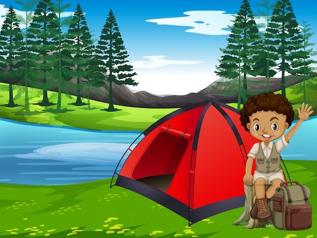 Un garçon campant en forêt Vecteur gratuit