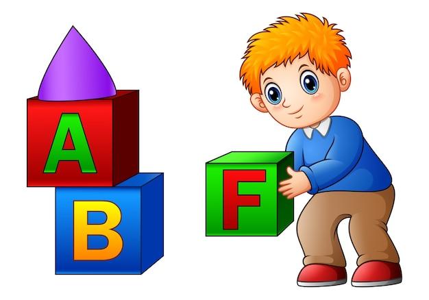 Garçon de dessin animé jouant avec des cubes de l'alphabet Vecteur Premium