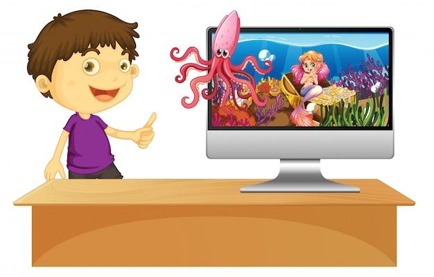 Garçon Heureux à Côté De L'ordinateur Avec Scène Sous-marine à L'écran Vecteur gratuit