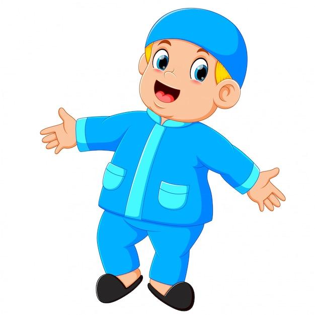 Un garçon heureux est debout et danse avec ses nouveaux vêtements bleus Vecteur Premium
