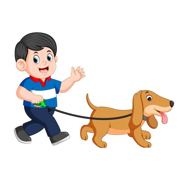 Garçon heureux qui marche avec son chien Vecteur Premium