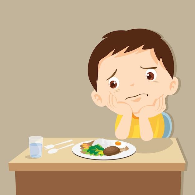 Garçon s'ennuie avec de la nourriture Vecteur Premium