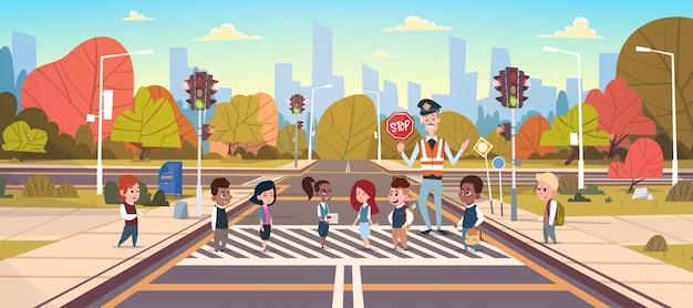 Un garde policier aide un groupe d'écoliers à traverser une route Vecteur Premium