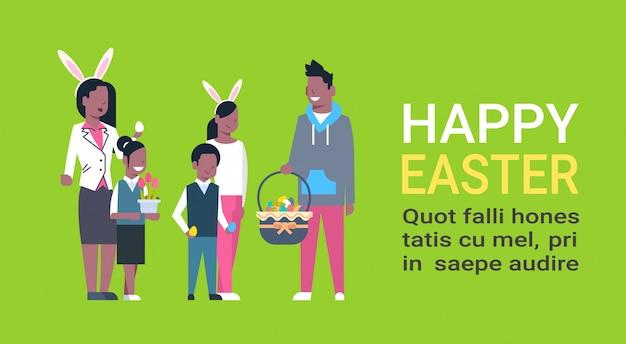 Grande famille afro-américaine joyeuses pâques. parents et enfants célèbrent les fêtes de fin d'année portent des oreilles de lapin Vecteur Premium