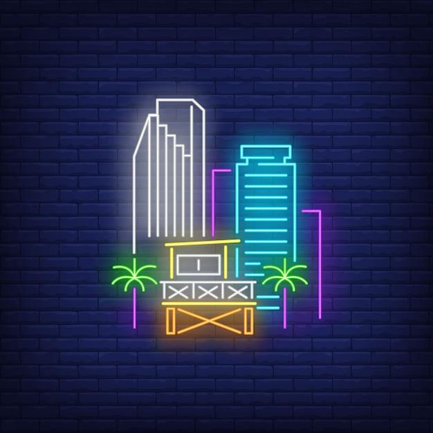 Gratte-ciel de la ville de miami et enseigne au néon de station de sauveteur. plage, tourisme, voyages. Vecteur gratuit