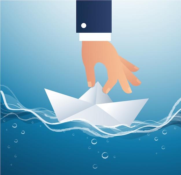 Grosse main tenant le vecteur de bateau en papier Vecteur Premium
