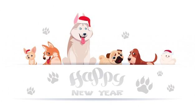 Groupe de chiens mignons assis sur fond blanc avec empreintes de pieds portant bonnet de noel asiatique bonne année Vecteur Premium