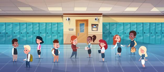 Groupe D'écoliers Dans Le Couloir De L'école Mix Race élèves Au-dessus De La Rangée De Casiers Vecteur Premium