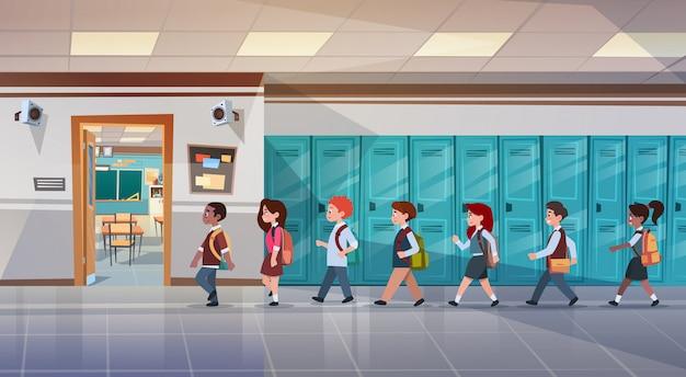 Groupe d'élèves marchant dans le couloir de l'école en salle de classe, élèves de race mixte Vecteur Premium