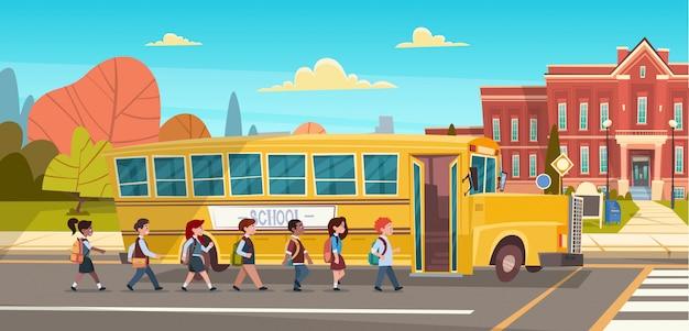 Groupe d'élèves mix race marche à pied pour bâtiment scolaire de bus jaune Vecteur Premium