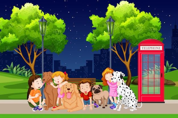 Groupe d'enfants et de chiens dans le parc Vecteur gratuit