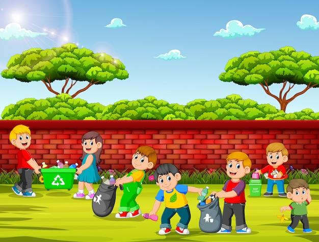 Un groupe d'enfants nettoyant le jardin Vecteur Premium