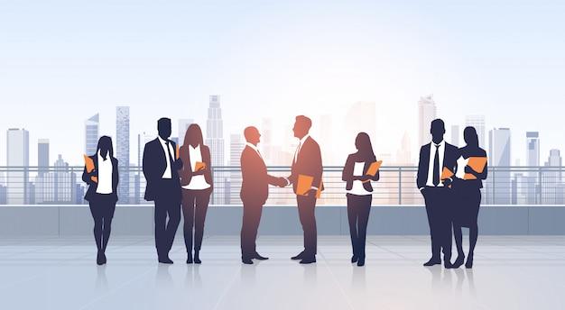 Groupe de gens d'affaires accord de réunion main serrer la main silhouettes moderne vue sur la ville immeuble de bureaux Vecteur Premium