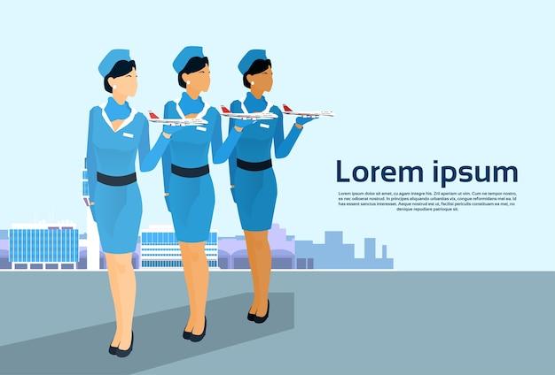 Le groupe de l'hôtesse de l'air détiennent des équipages d'avions au-dessus de l'aéroport Vecteur Premium