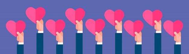 Groupe de mains tenant coeur rose en forme de saint valentin concept bannière horizontale Vecteur Premium